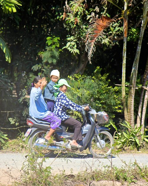 Kid standing on moped in Chiang Mai, Thailand