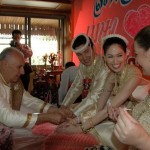 Jack tying our wrists at Thai wedding of our Wedding World Tour